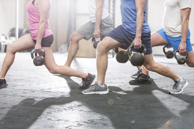Low section of people lifting kettlebells at crossfit gym